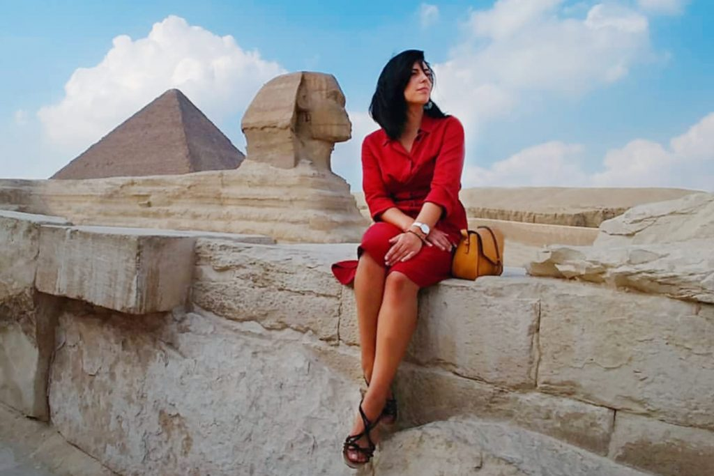 a girl is sitting next to the Pyramids and sphinx of Giza Egypt