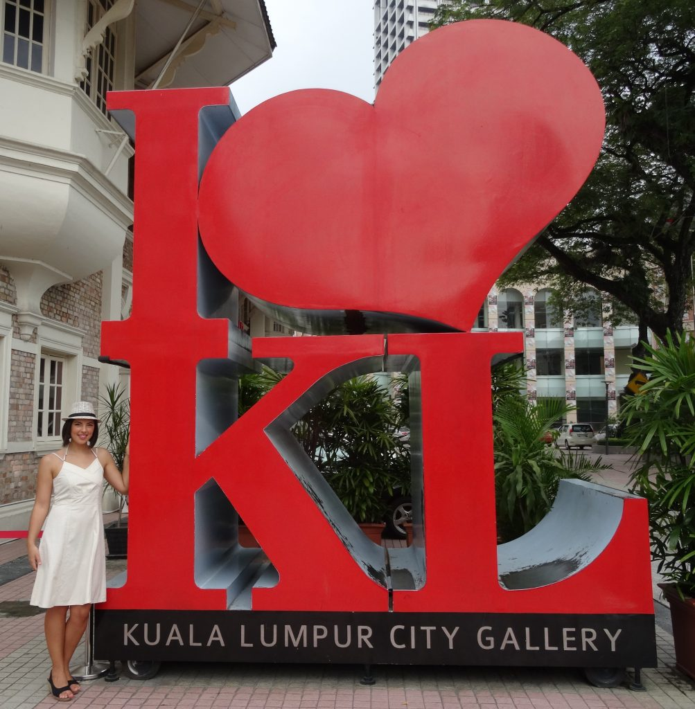 a girl is standing next to a big sign I love KL