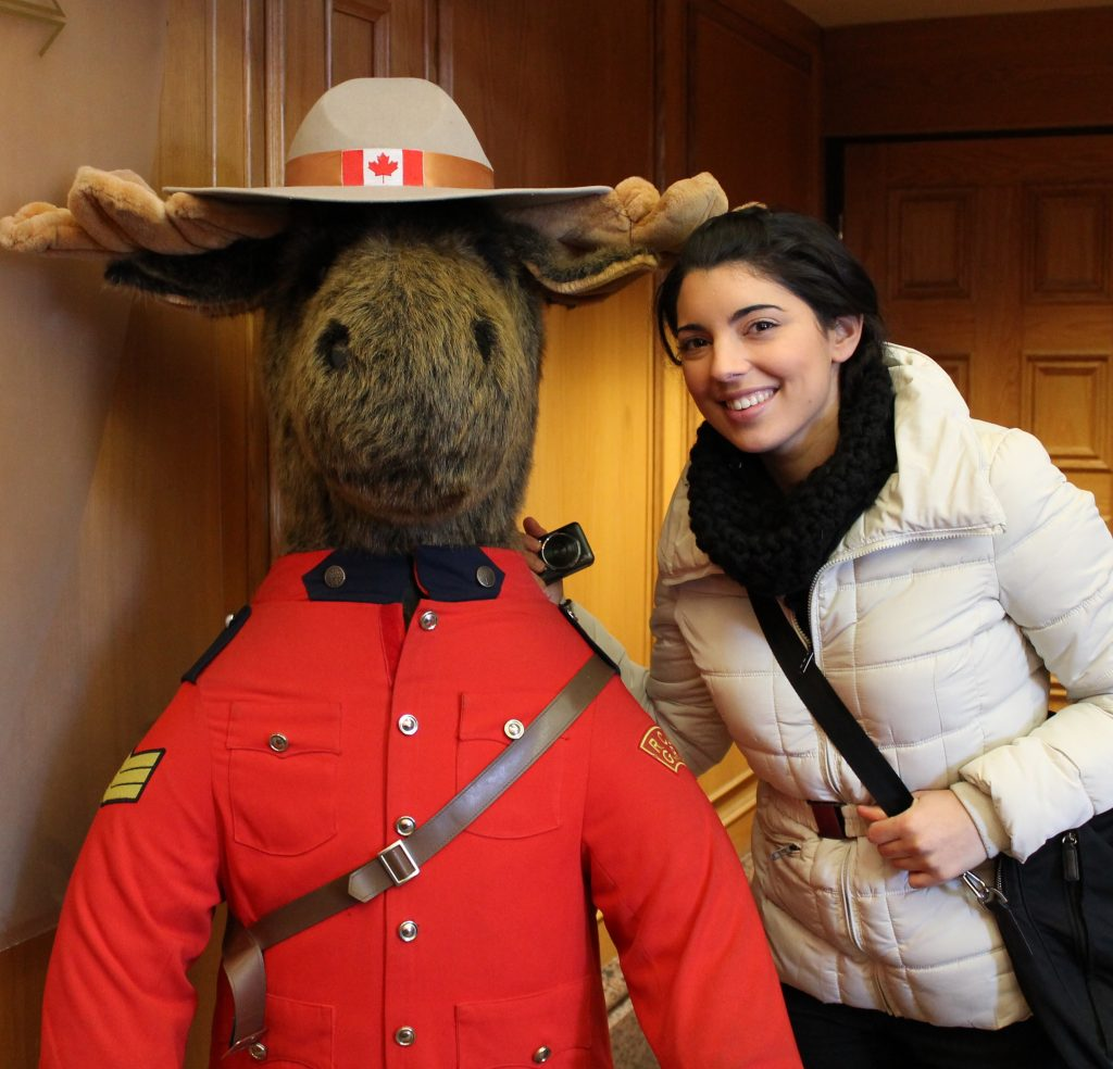 a girl is standing next to a big moose plush