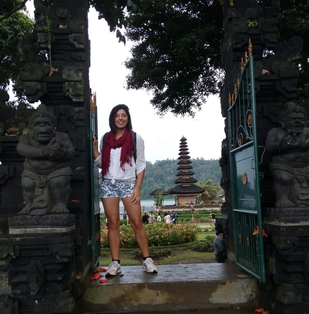 a girl is standing in front of Pur Ulun Dalu Temple in Bali