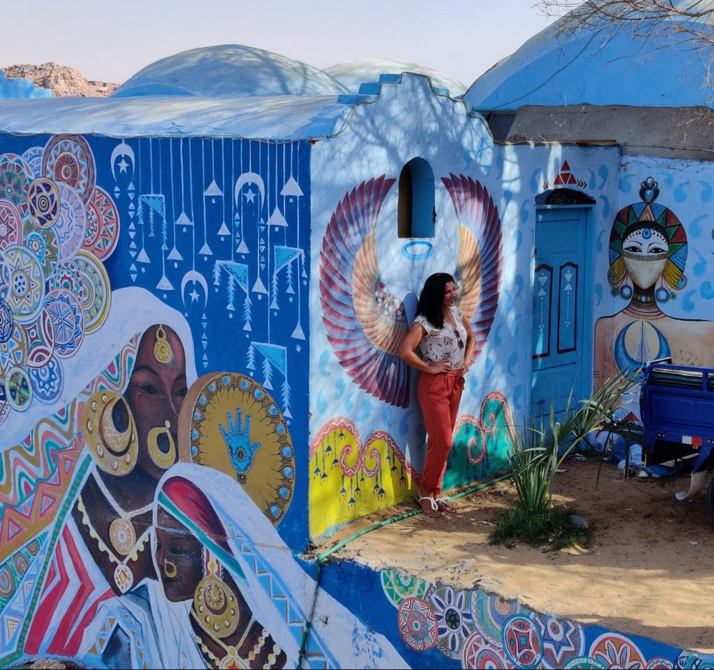 a girl is standing next to a decorated house in the Nubian Village - Aswan