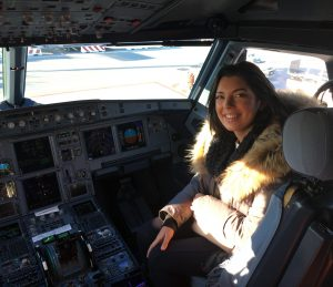 a girl is sitting in the cockpit of a plane