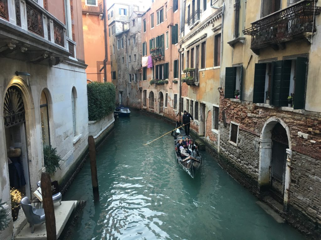 a man is riding a gondola in a small Venetian canal