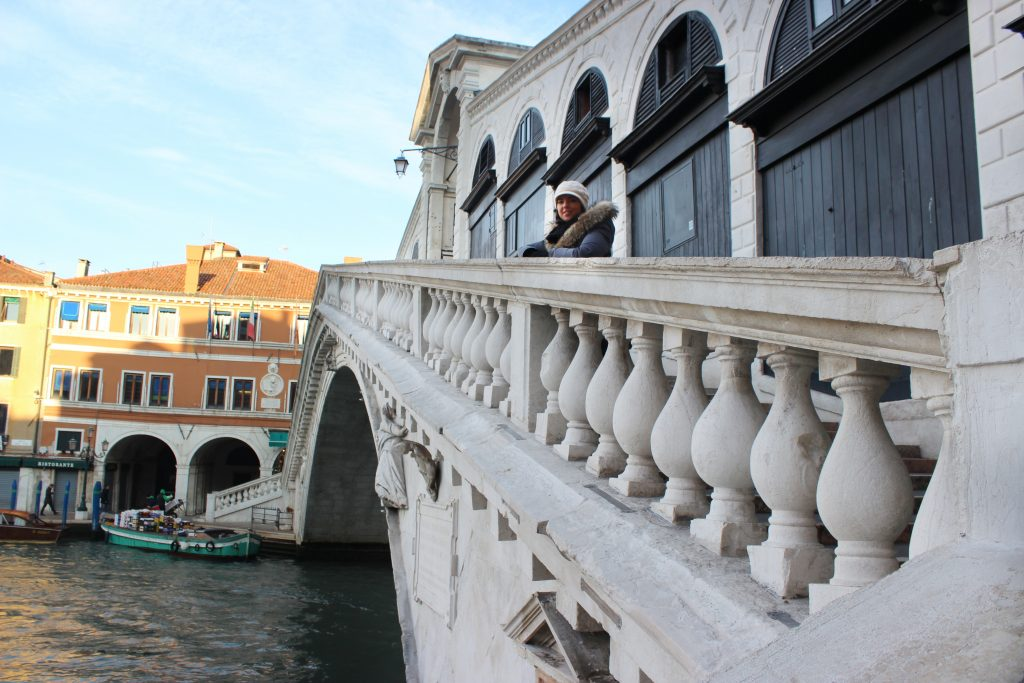 a girl is standing in the middle of Rialto bridge in Venice