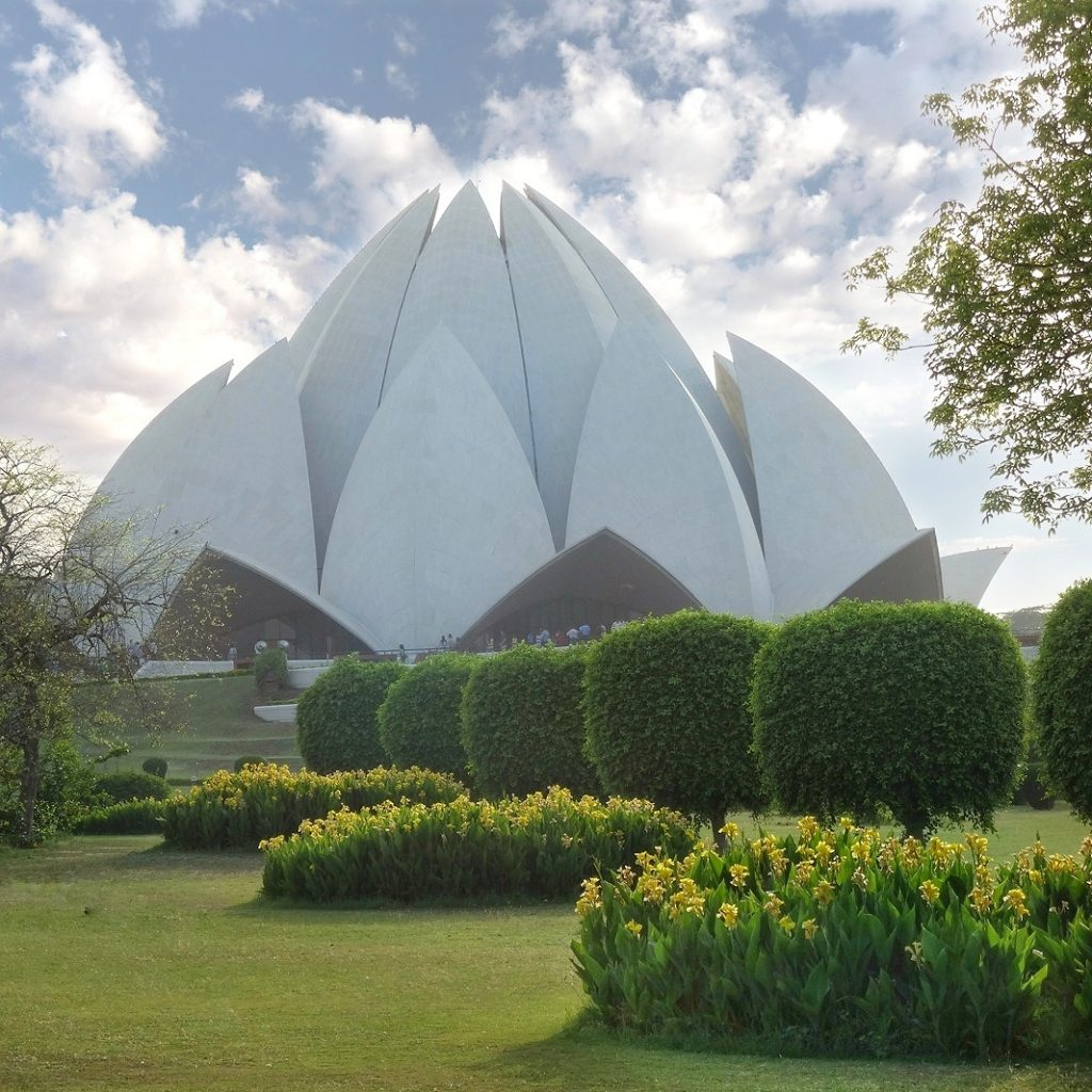 the flower shape building rises in the middle of beautiful gardens