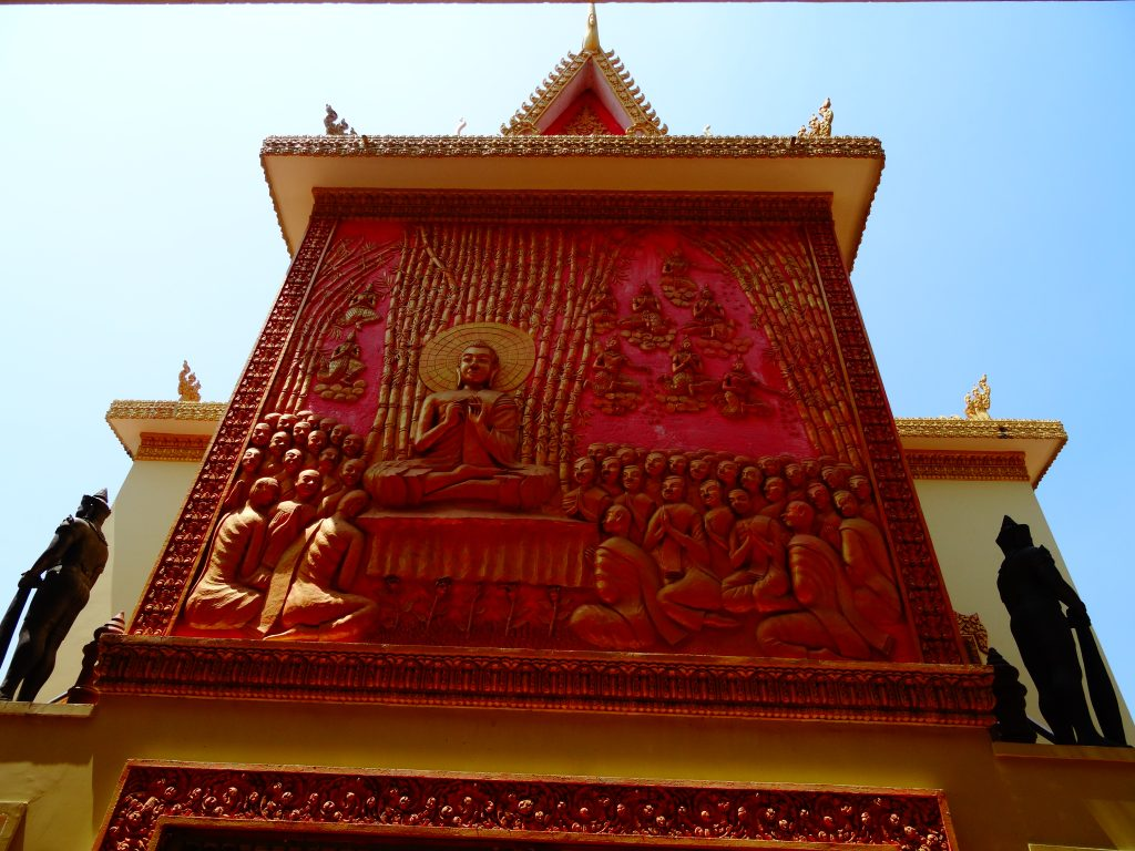 red sculpture of the buddha surrounded by monks at the Wat Ounalom