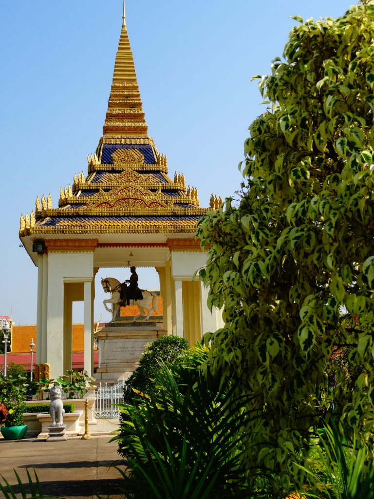 a golden stupa shelters the statue of ancient kign riddign a horse inside the royal palace