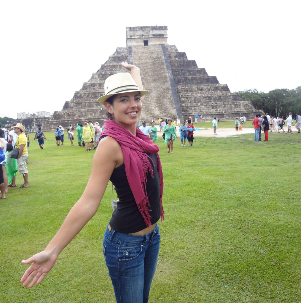 a girl is standing in front of Chichen Itza