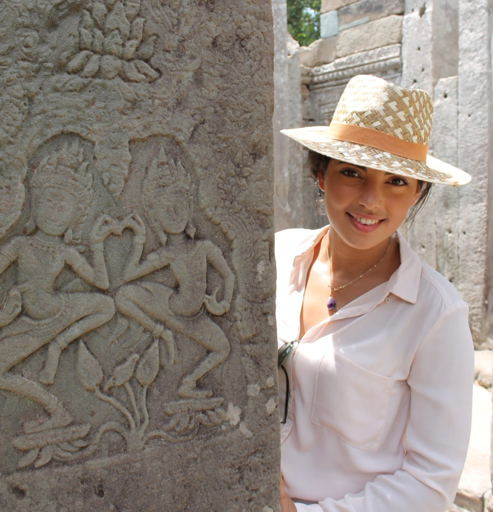 a girl is standing next to a sculpture in Angkor Wat