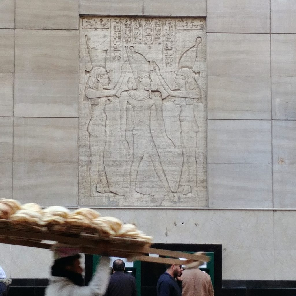 an egyptian man carries fresh bread in the street, there is wall decoration in the background with Egyptian hieroglyphs