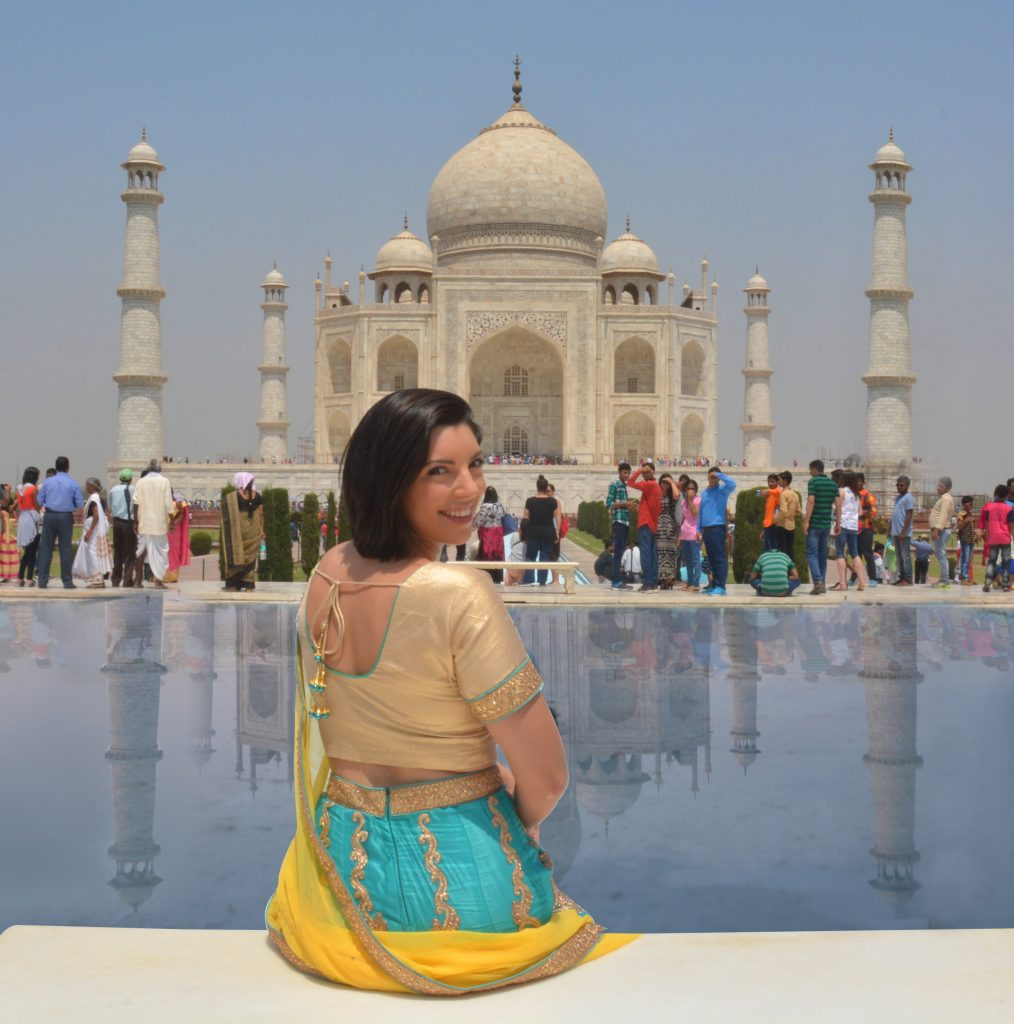 a girl sitting in front of Taj Mahal