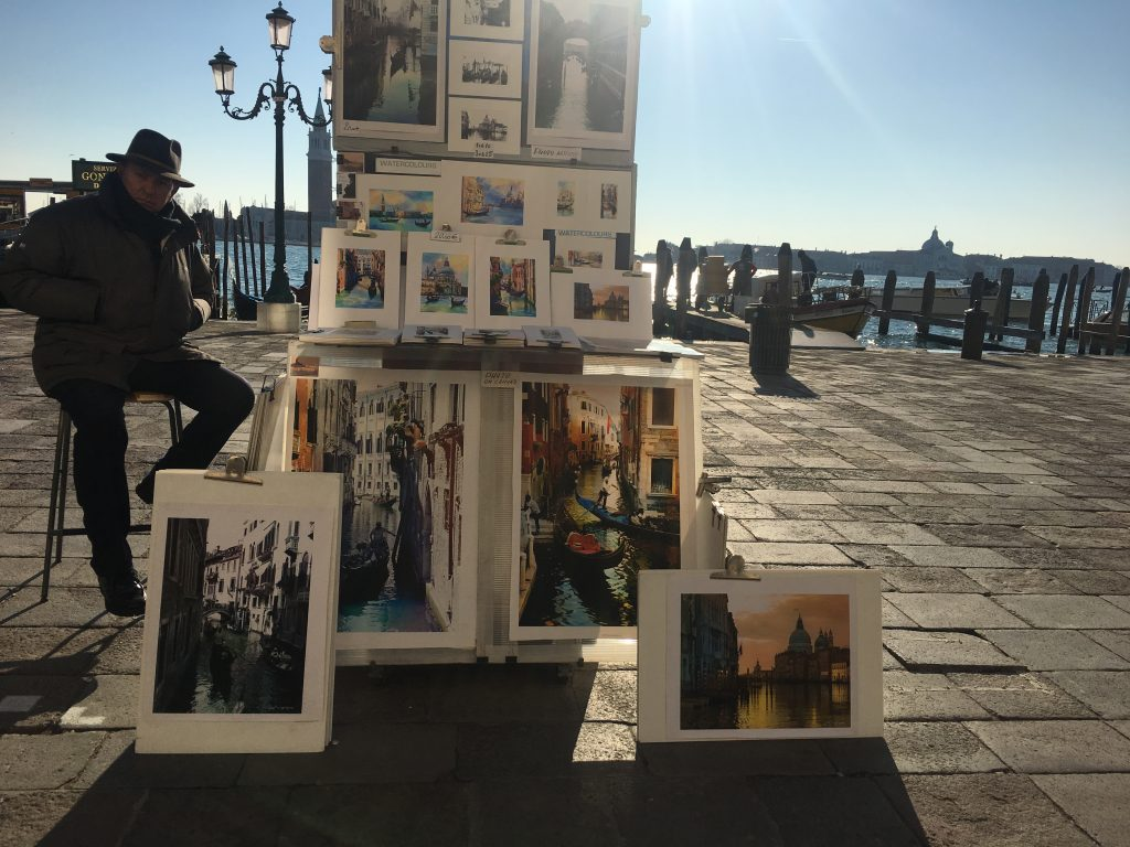 a man is selling souvenirs on the river banks of Venice
