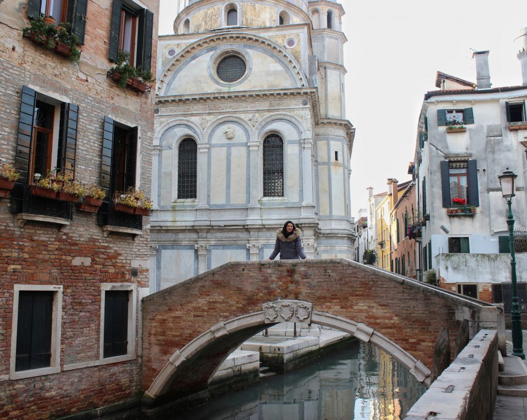 a girl is standing in the middle of a bridge in Venice