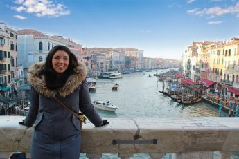 a girl is sitting on the Rialto bridge with view of the grand Canal in Venice