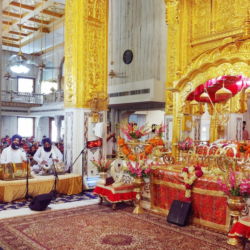 the main room for prayers is so colorful with gold pilars