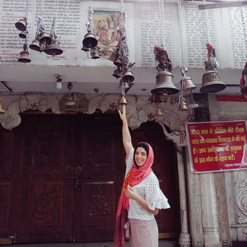 a girl is touchign the bells hanging from the ceiling for good fortune