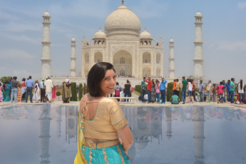 a girl is sitting on the bench in front of Taj Mahal