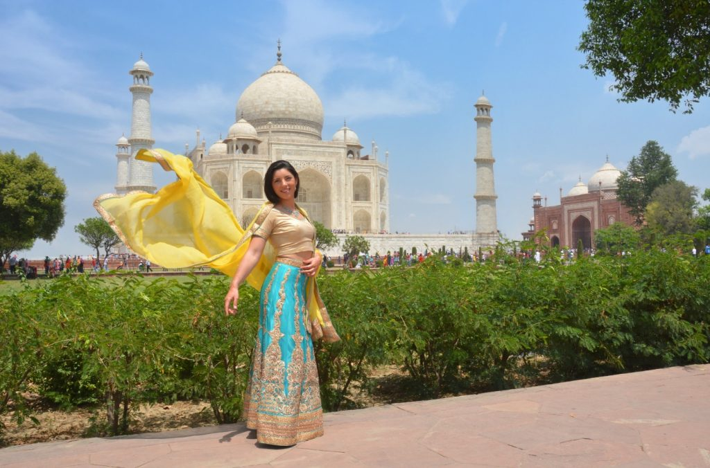 a girl in saree is posign in front of the Taj Mahal