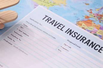 a travel insurance contract surrounded by passport and flight tickets