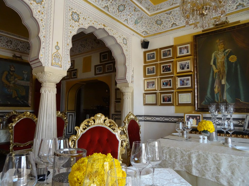 decor inside the restaurant, a portrait of the king of Jaipur stands in front of the guests' tables